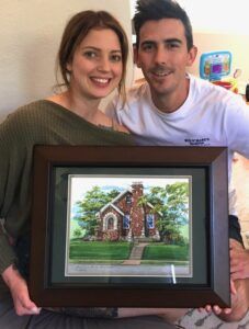 Young couple showing their house portrait gift
